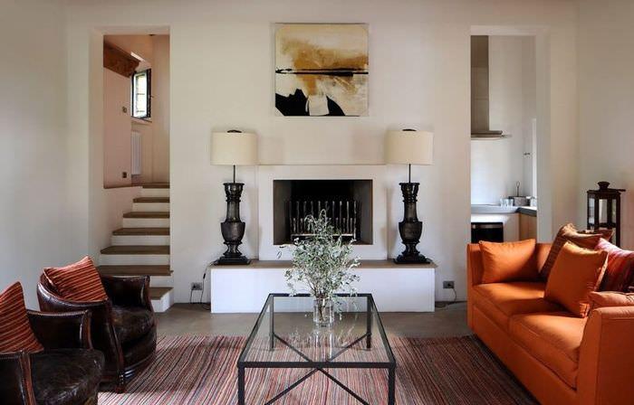 Оранжевый диван в интерьере гостиной с камином