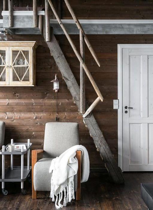 Серое кресло под крутой лестницей на второй этаж деревянного дома