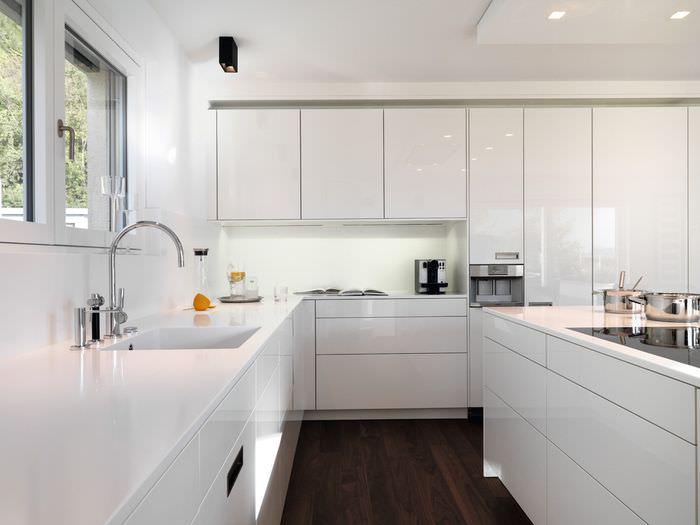 Интерьер белой кухни угловой планировки с островом