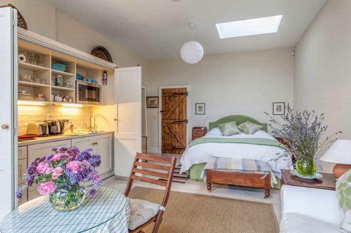 Интерьер квартиры с кухней и спальней в общей комнате