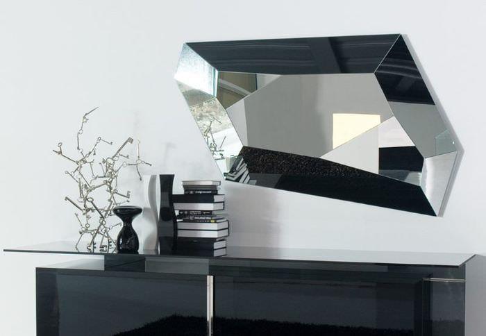 Зеркало нестандартной формы над тумбой с глянцевыми поверхностями