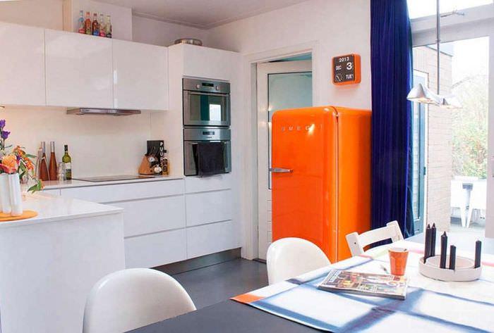 Оранжевый холодильник в кухне с белым гарнитуром