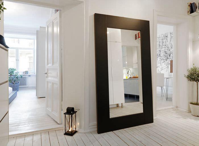 Зеркало в широкой черной раме на полу белого коридора