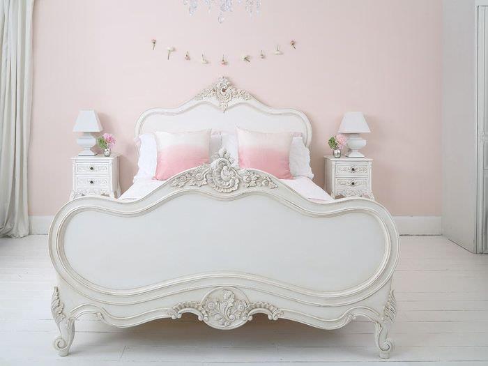 Интерьер белой спальни с розовой стеной