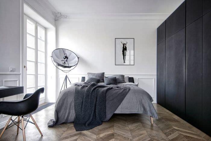 Черный шкаф в спальне с белыми стенами