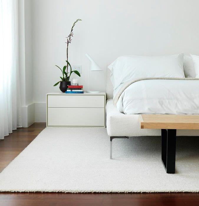 Белый ковер на полу спальни в стиле минимализма