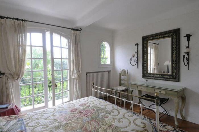 Интерьер спальни с дверью на балкон