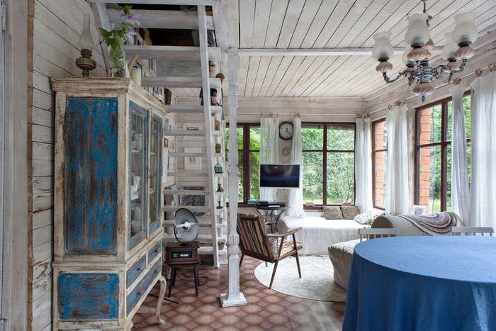 Небольшая гостиная с лестницей на второй этаж дачного домика