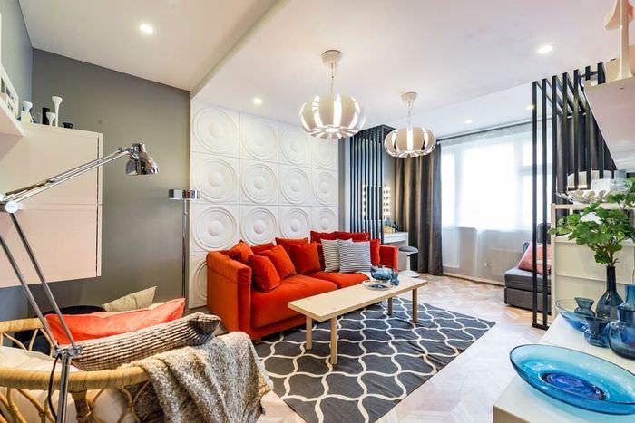 Красный диван возле акцентной стены гостиной