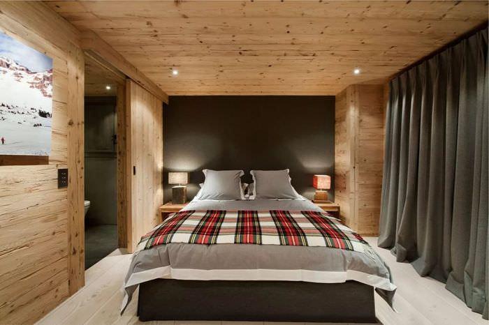 Темные шторы в интерьере спальни срубового дома