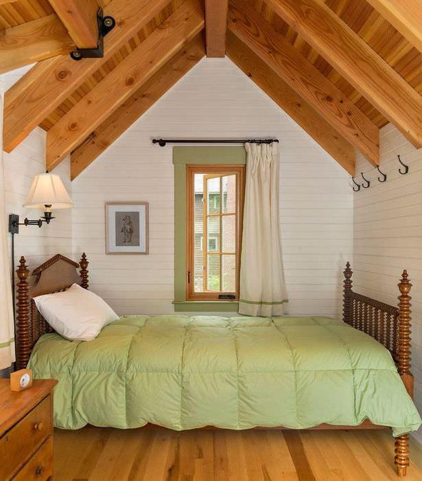 Интерьер небольшой спальни в мансарде деревянного дома