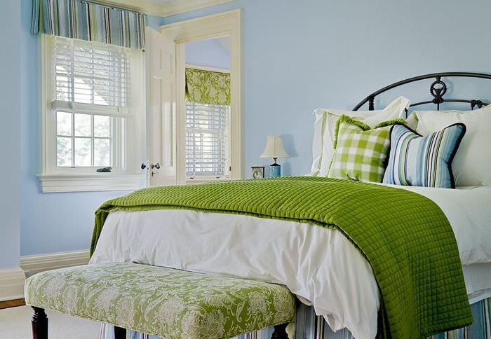 Зеленое покрывало на кровати в спальне с голубыми стенами