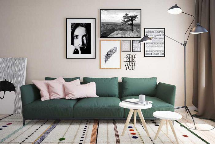 Украшение фотографиями стены над темно-зеленым диваном