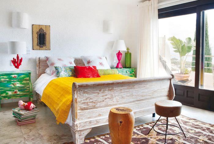 Желтое покрывало на деревянной кровати