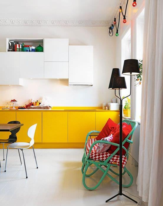 Желтые тумбы кухонного гарнитура на фоне белой стены