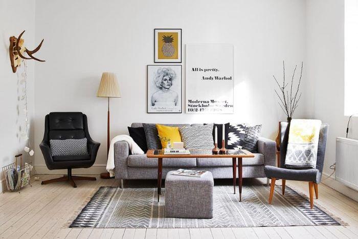 Черное кресло рядом с серым диваном в белой гостиной