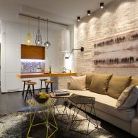 Прямой диван возле кирпичной стены белого цвета