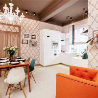 Оранжевое кресло и красный диван в кухне-гостиной