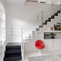 Красное кресло на фоне белой стены