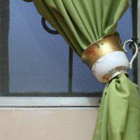Фарфоровая кружка в роли зажима для шторы на кухне