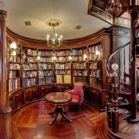 Винтовая лестница в холле с книжными шкафами