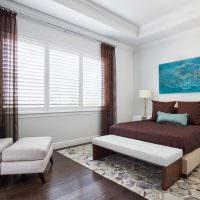 Голубая картина на белой стене спальни