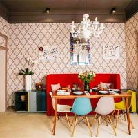 Красный диван и разноцветные стулья