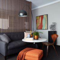 Темно-серый диван и круглый стол белого цвета