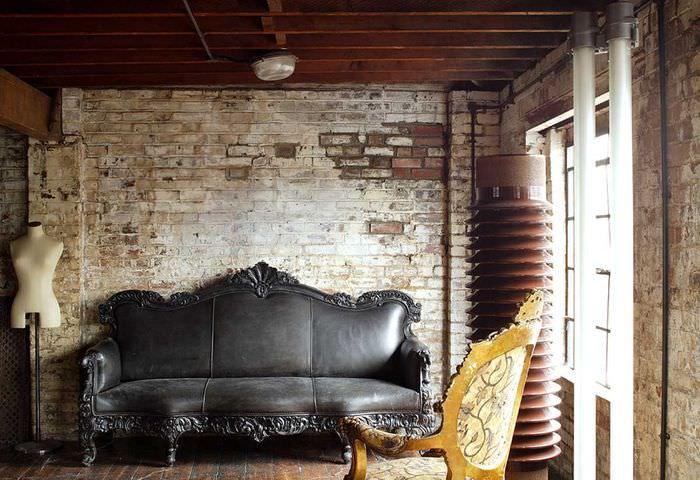 Черный диван около грубо отделанной кирпичной стены