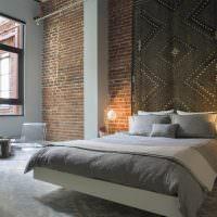 Ковер над изголовьем кровати в спальне с кирпичной стеной