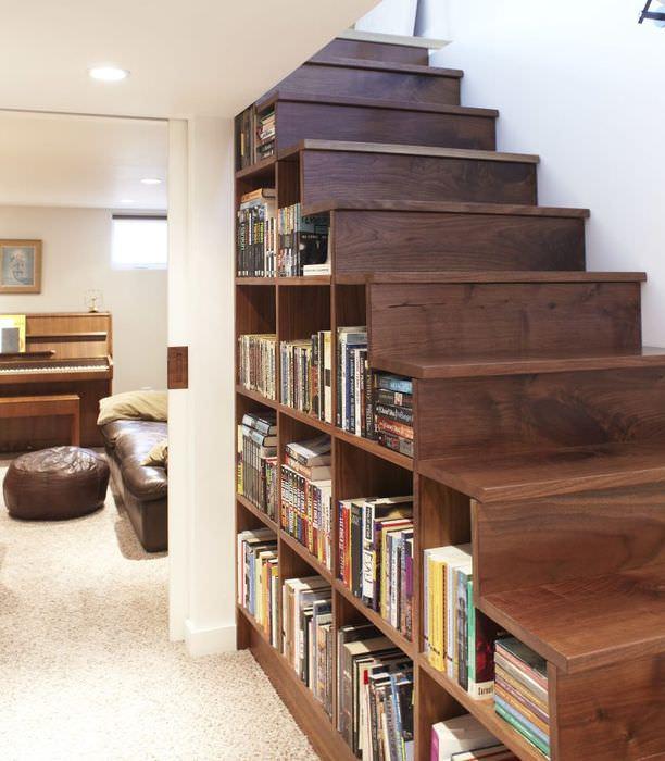 Книжные полки под лестницей на второй этаж частного дома