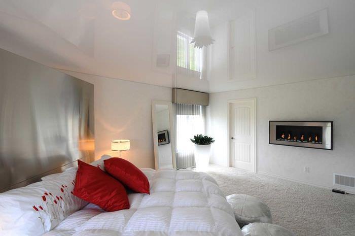 Две красные подушки на белом покрывале кровати
