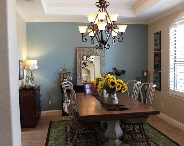 Люстра с коваными элементами над обеденным столом в гостиной частного дома