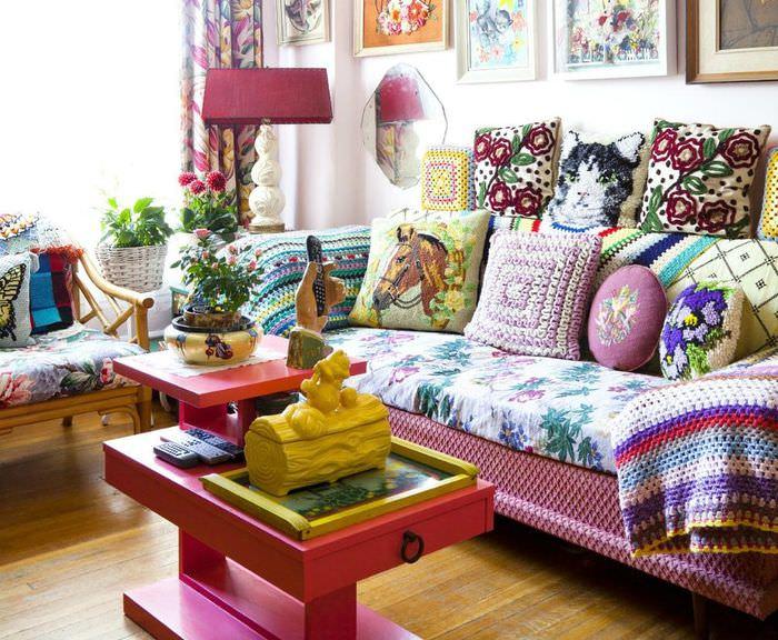 Разномастные подушки на диване с пестрым покрывалом