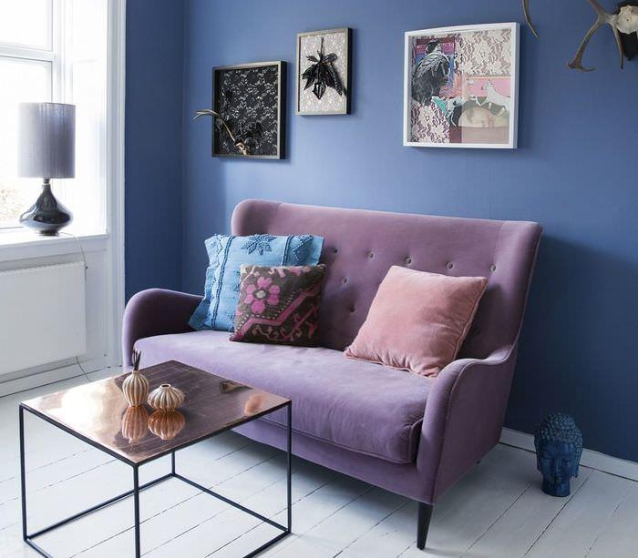 Небольшой диванчик на фоне синей стены