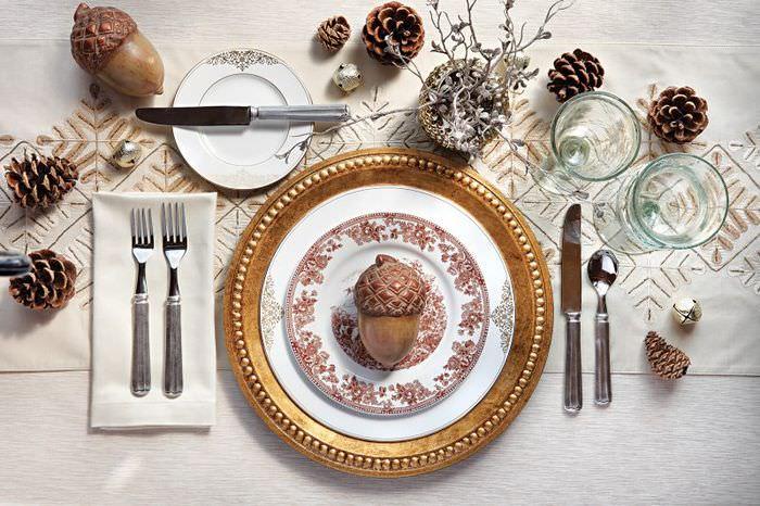 Шишки на столе с золотистой посудой