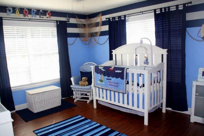 Белая кроватка для младенца в комнате с синими шторами