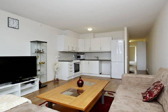 Белый кухонный гарнитур угловой планировки в кухне-гостиной 20 кв м