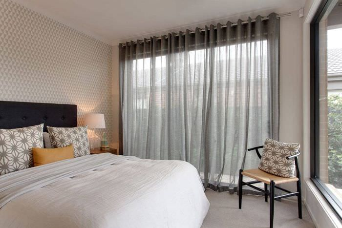 Интерьер спальни с легкими занавесками серого тона