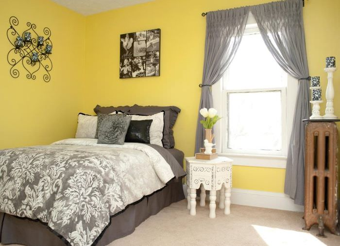 Полупрозрачные занавески серого тона в спальне с желтыми стенами