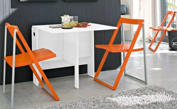 Один из вариантов экономии пространства складные стулья, после обеда их можно убрать в укромный уголок и не натыкаться на них каждый раз во время готовки.