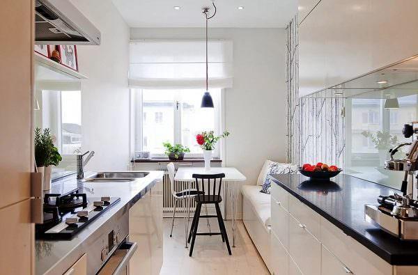 Чтобы отделить ту зону кухни, на которой происходит непосредственное приготовление еды и другие бытовые дела, от трапезной, стоит всего лишь соорудить обычную нишу и уже в ней расположить стол.