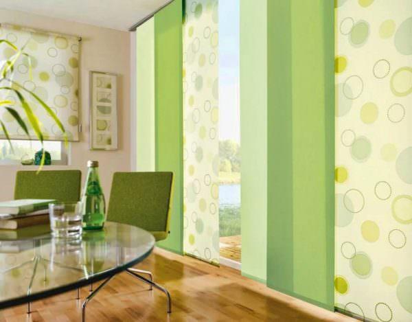 Новинки дизайна штор для зала 2019 на фото в комнатах, наполненных декоративными элементами, представлены лаконичными моделями портьер и японских штор светлых оттенков.